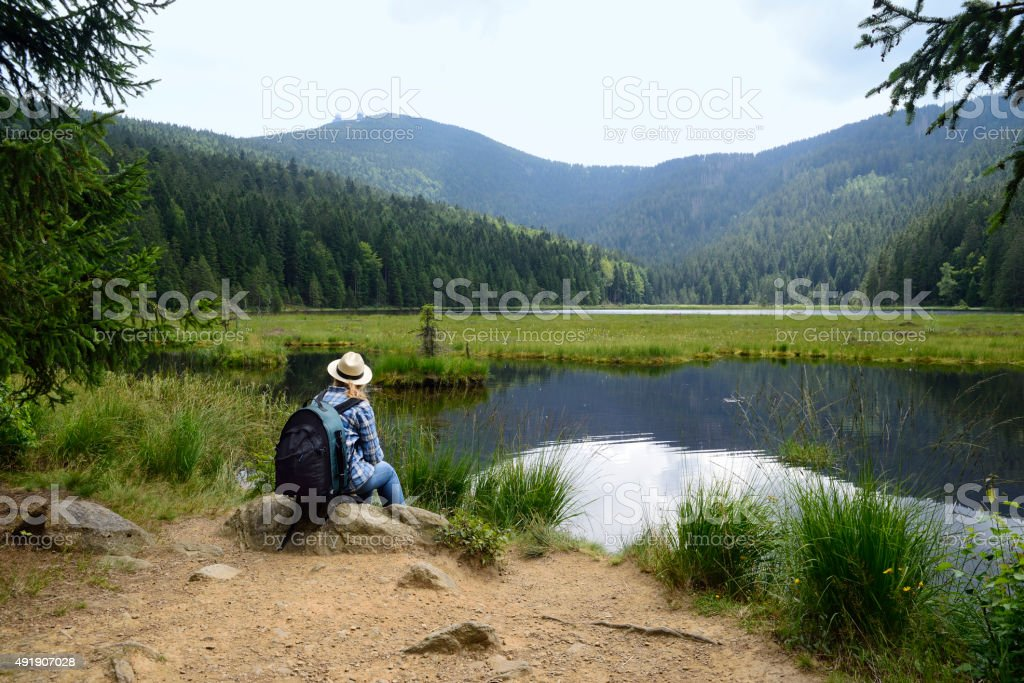 Hiking woman at a lake in the mountains stock photo