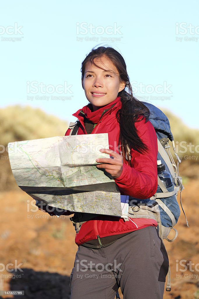 Hiking woman in nature holding map stock photo