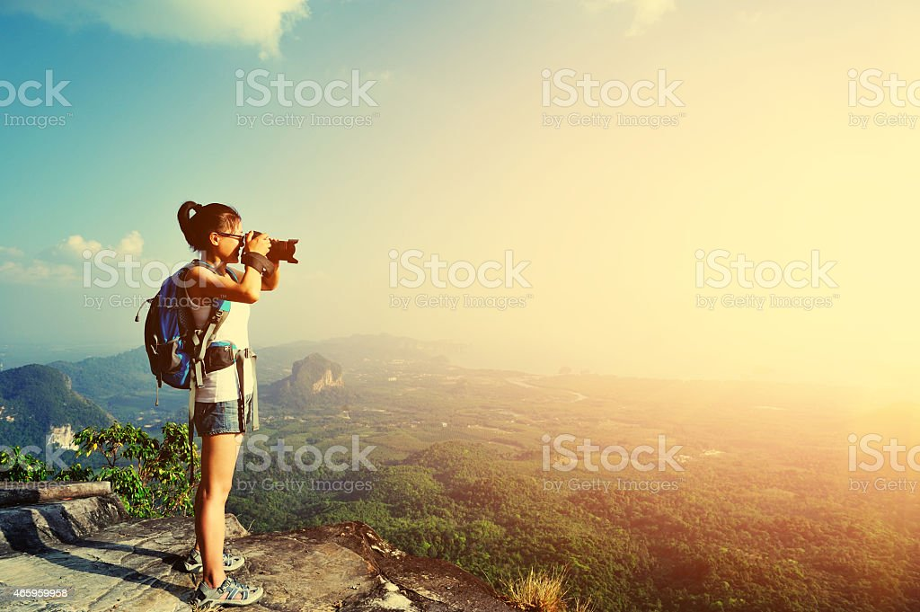 hiking woman photographer  taking photo  on mountain peak stock photo