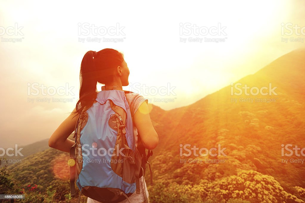 hiking woman stand at mountain peak stock photo
