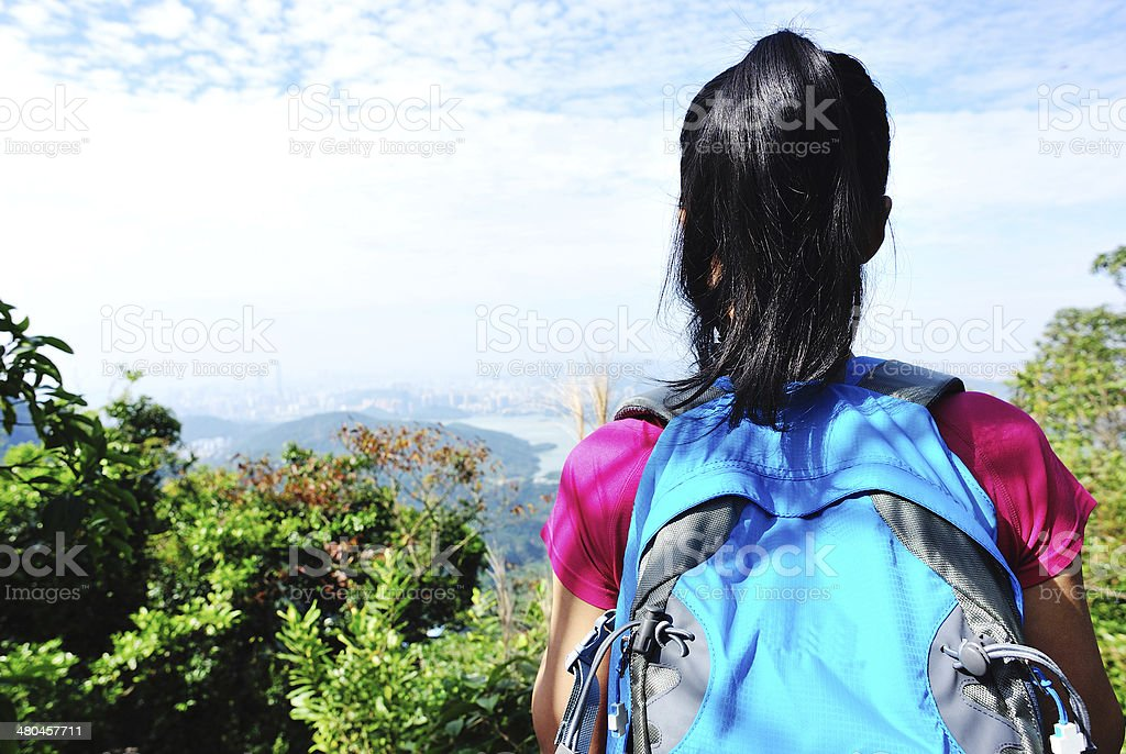 hiking woman stand mountain peak looking at the view stock photo
