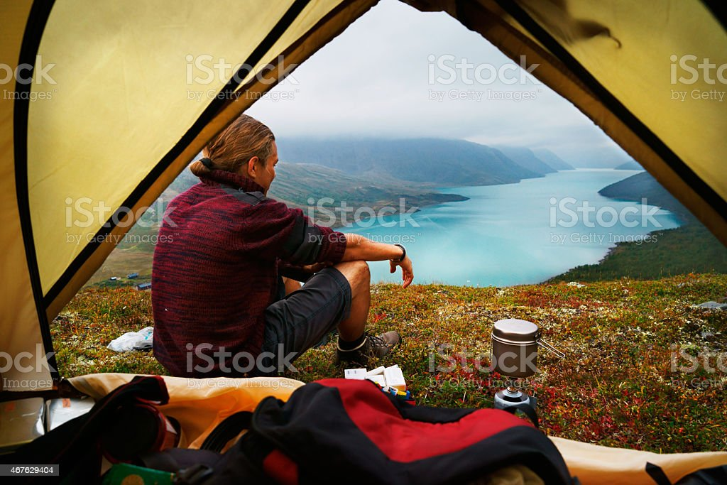 Hiking young man and scenic view of lake Gjende Jotunheimen stock photo