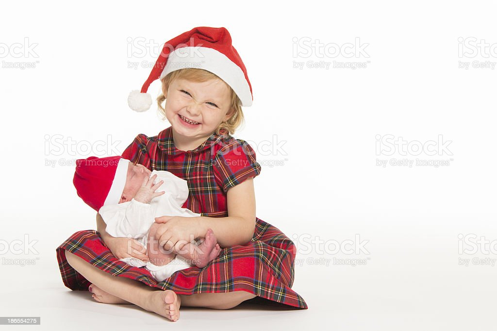 Hilarious blonde girl in santa hat holding baby royalty-free stock photo