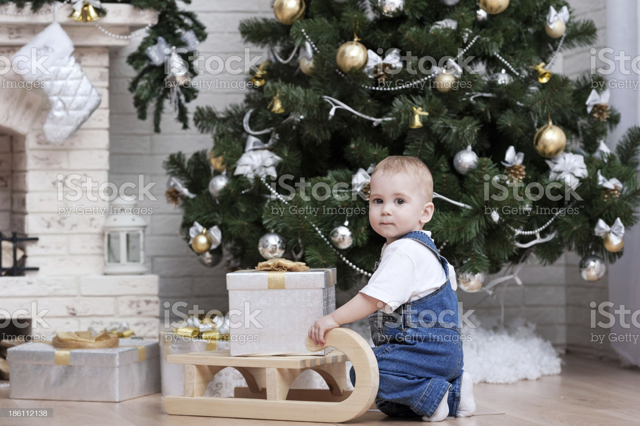 ?hild on a sled with gift of the Christmas tree royalty-free stock photo