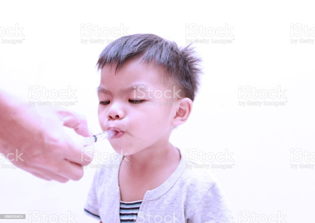 Сhild taking cough syrup on a syringe. stock photo