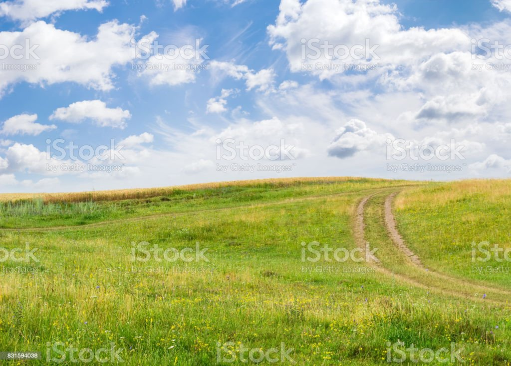 Hill with dirt track against wheat field and sky stock photo