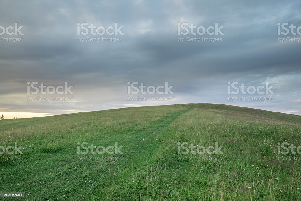 Hill with green grass on background of sky and thunderclouds stock photo