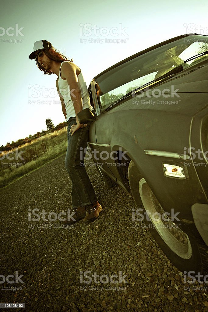 Hillbilly Man Leaning Against Car on Road stock photo
