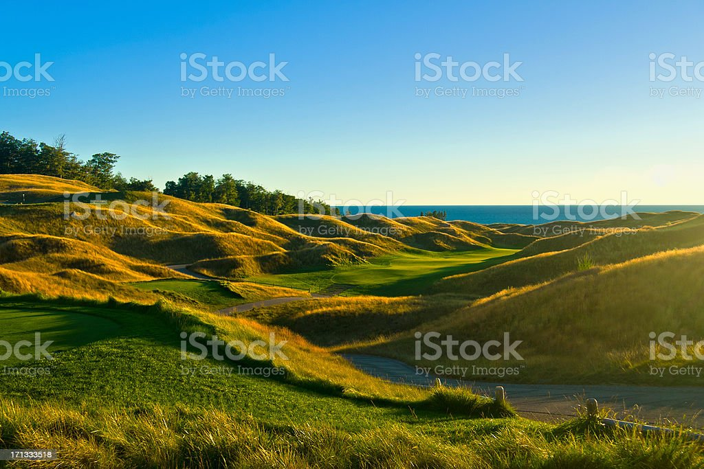 Hills of a golf course with the sun in the background stock photo