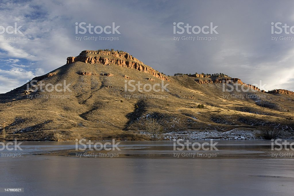 hills, sandstone cliffs and freezing lake in Colorado stock photo