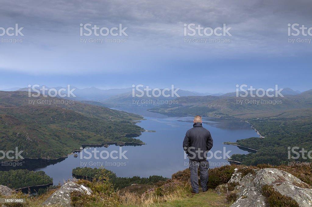 Hillwalker enjoying view of Loch Katrine at dawn. stock photo