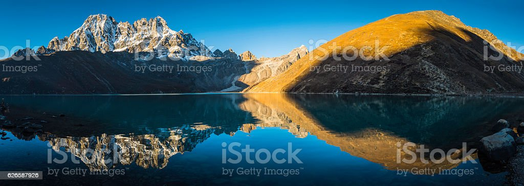 Himalaya mountain peaks reflecting in tranquil Gokyo Lake panorama Nepal stock photo