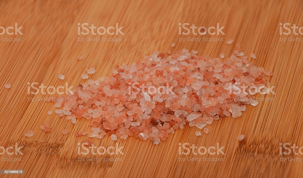 Himalayan pink salt batch over wooden bamboo background, angle v royalty-free stock photo