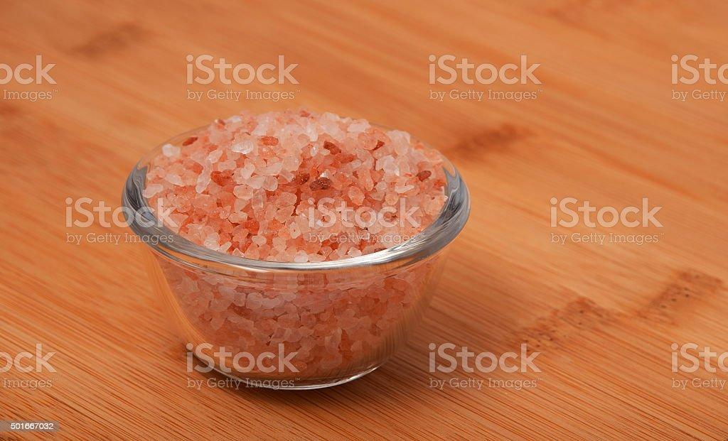 Himalayan pink salt in tiny transparent glass bowl on wood royalty-free stock photo