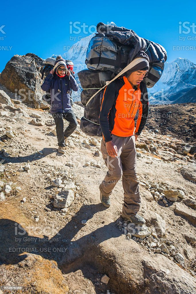 Himalayas porters carrying expedition kit Everest base camp trail Nepal stock photo