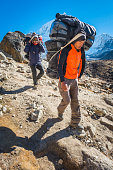 Himalayas porters carrying expedition kit Everest base camp trail Nepal