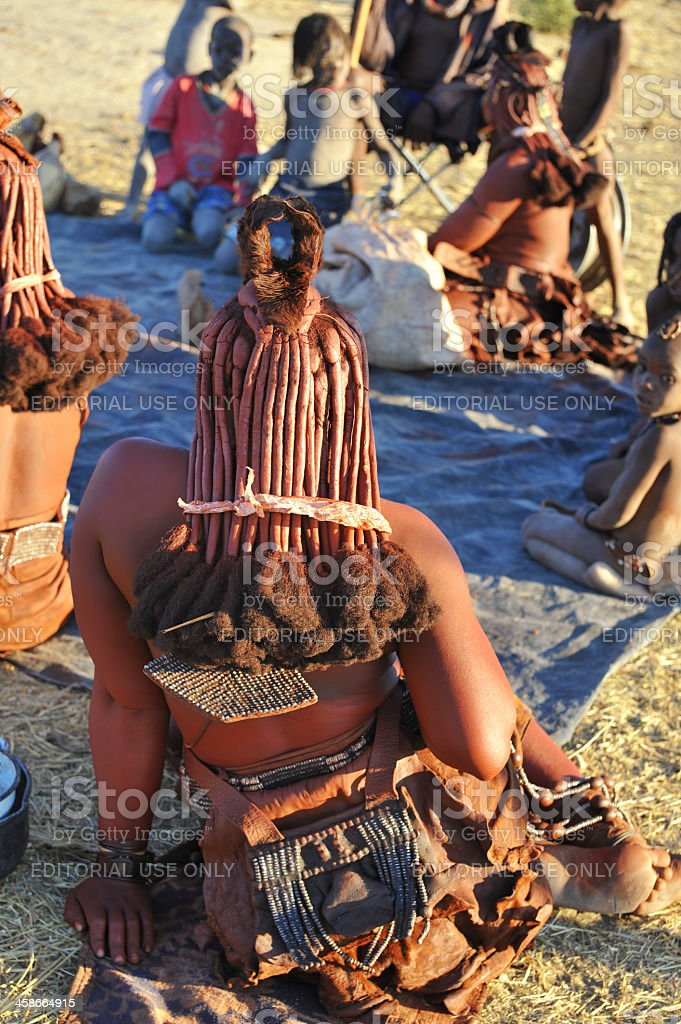 Himba family sitting together in village near Opuwo,Namibia stock photo