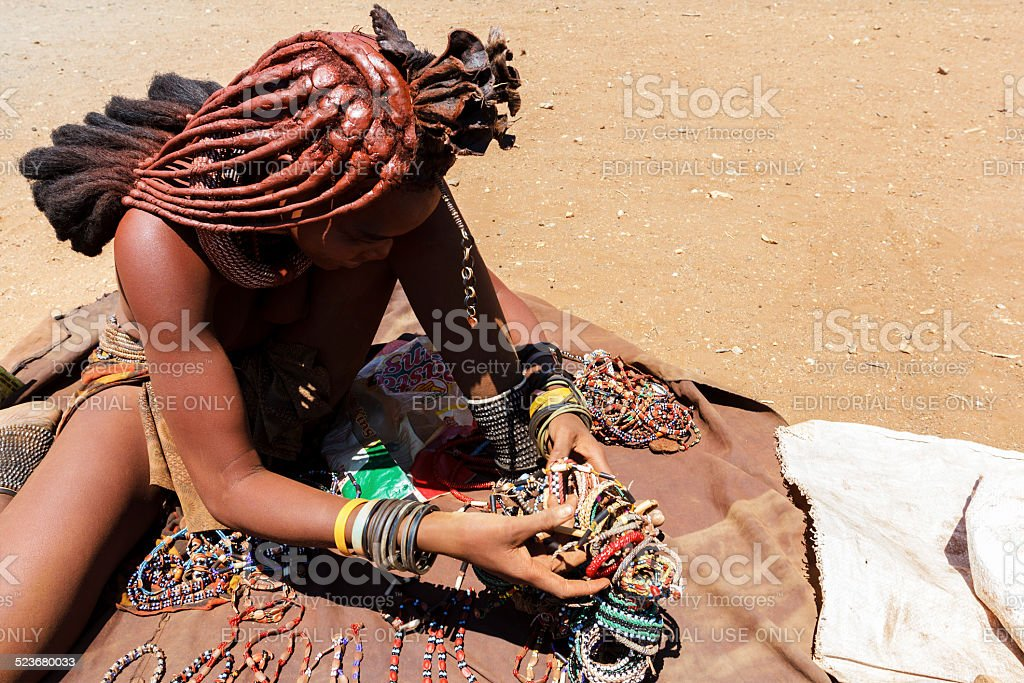 Himba girl with souvenirs for sale in traditional village stock photo