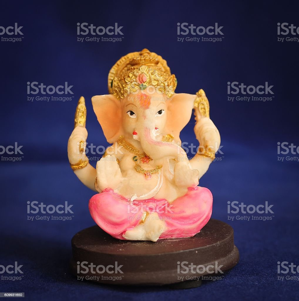 Hindu God Ganesha Statue on dark blue background stock photo