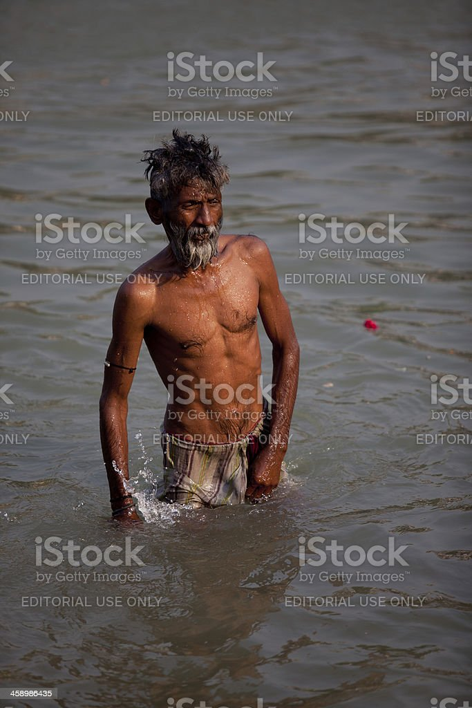 Hindu man baths in holy Ganges River royalty-free stock photo