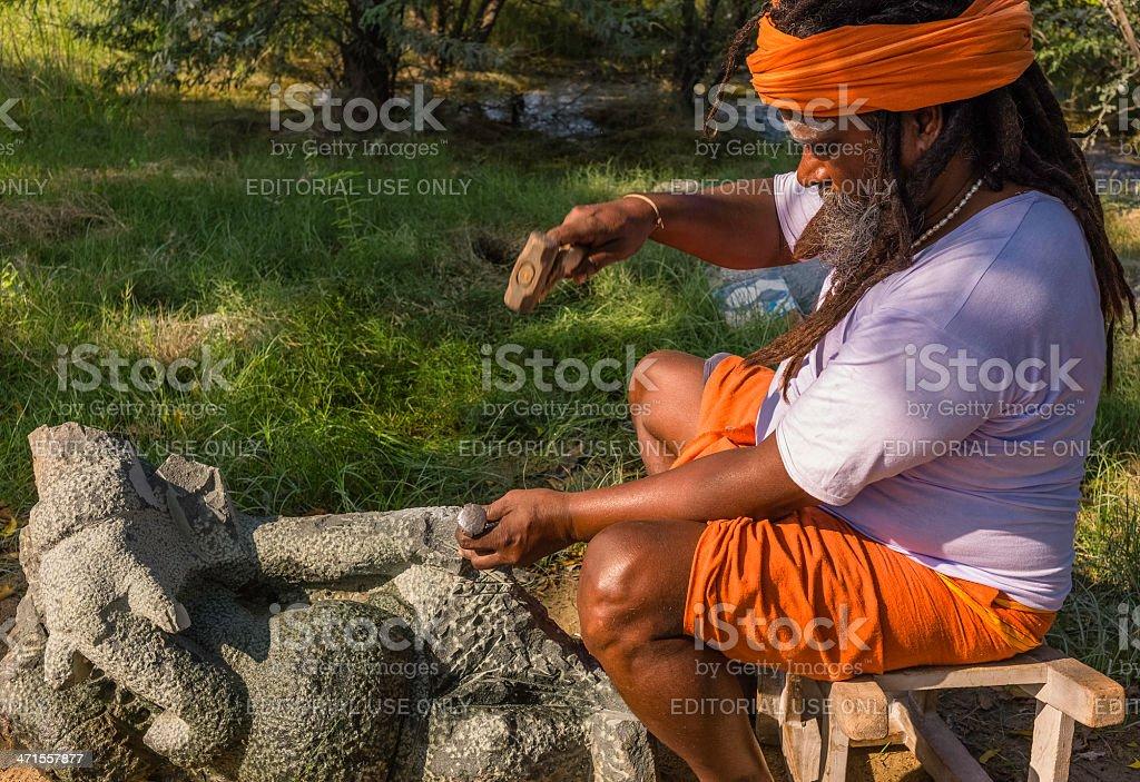 Hindu priest carving stone God, Mamallapuram, Tamil Nadu, India. stock photo