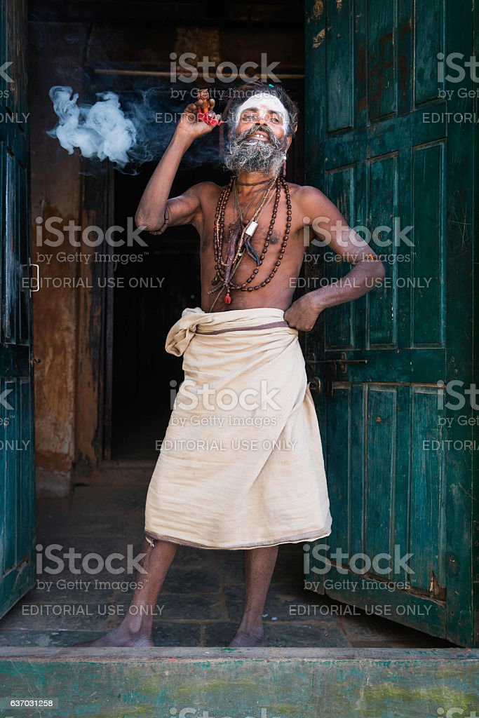 Hindu Sadhu holy man smoking charas outside temple Kathmandu Nepal stock photo