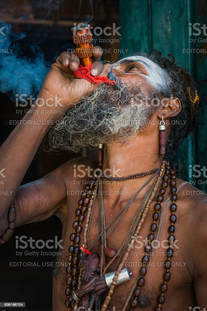 Hindu Sadhu holy man smoking charas pipe Kathmandu temple Nepal stock photo