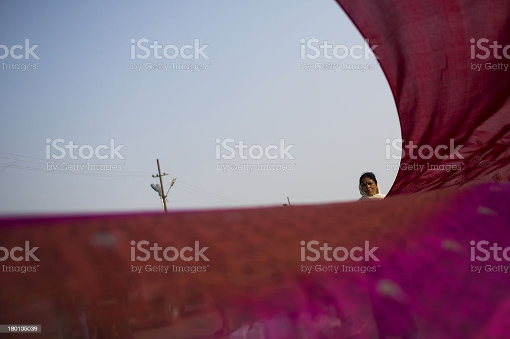 Hindu woman dries a sari on the river side stock photo