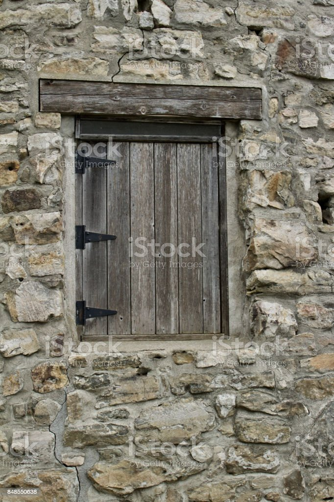 Hinged wooden window entrance to old stone gristmill building stock photo