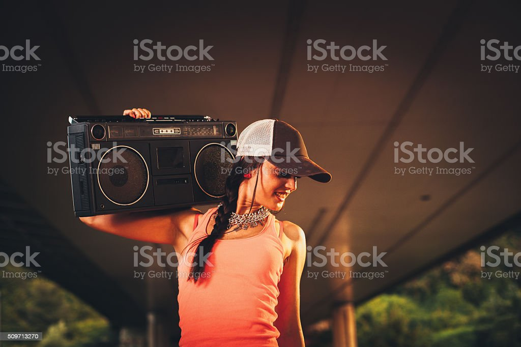 Hip hop woman holding a tape recorder on shoulder stock photo