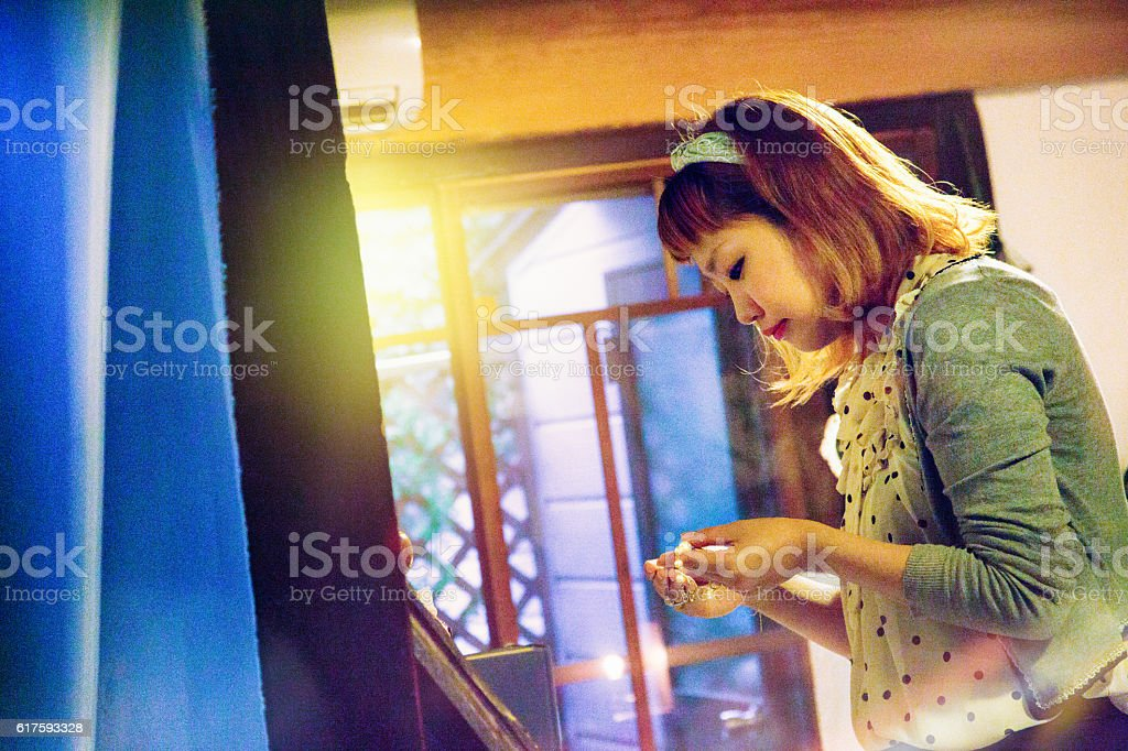 Hip Japanese female looking at jewelry in small shop stock photo