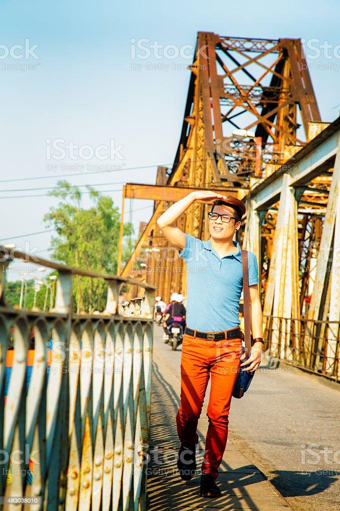 Hip Vietnamese male student crossing long bien bridge Hanoi vietnam stock photo