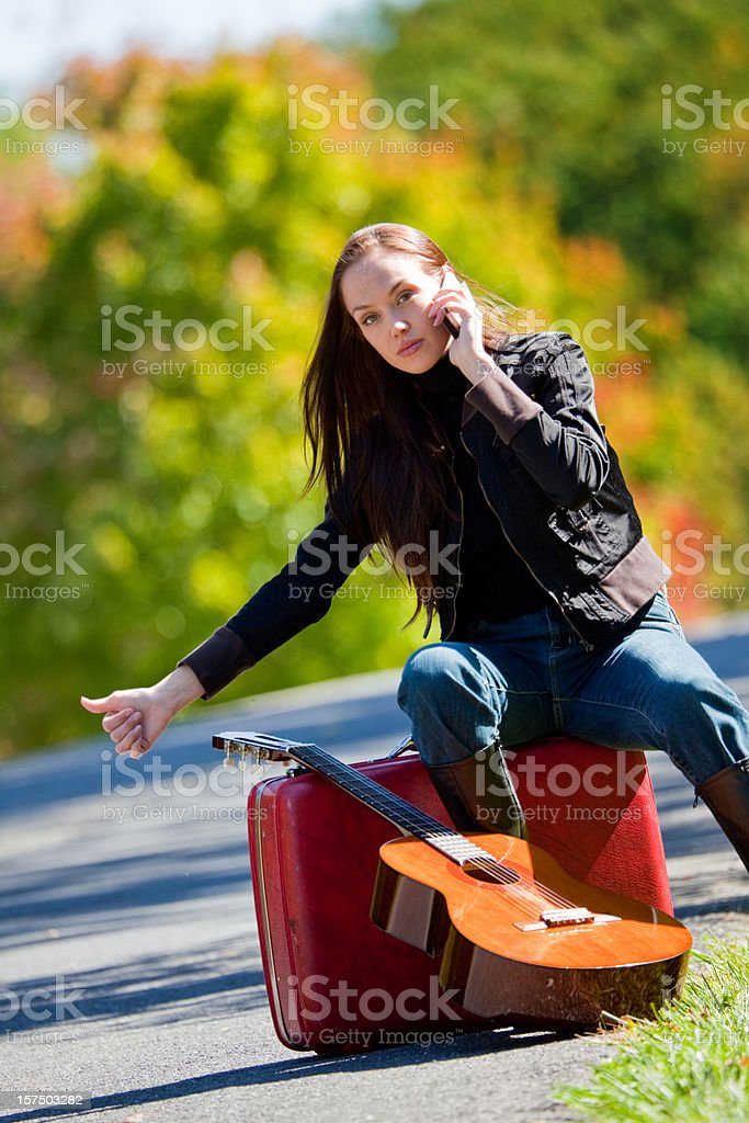 Hip woman hitchhiking on her cell phone royalty-free stock photo