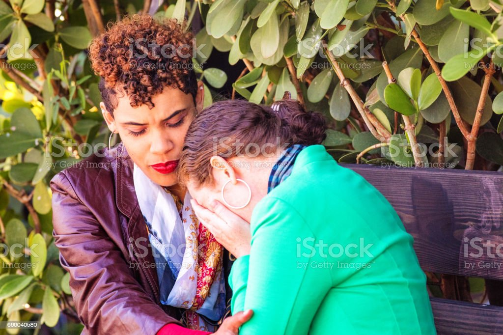 Hip young urban female consoling her crying friend stock photo