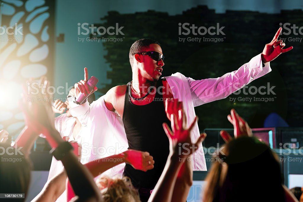 Hip-hop musician performing on stage with a crowd stock photo