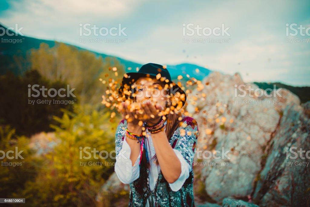 Hippie girl blowing confetti stock photo