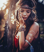 Hippie girl outdoors with jewelry and temporary gold foil tattoo