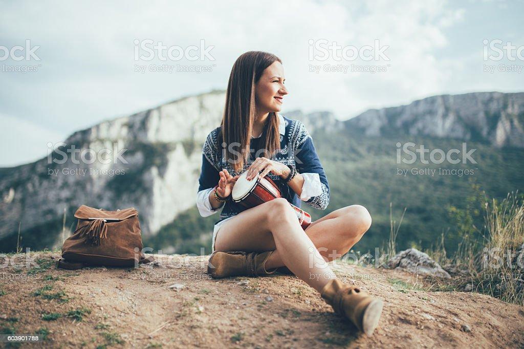 Hippie girl playing drum stock photo