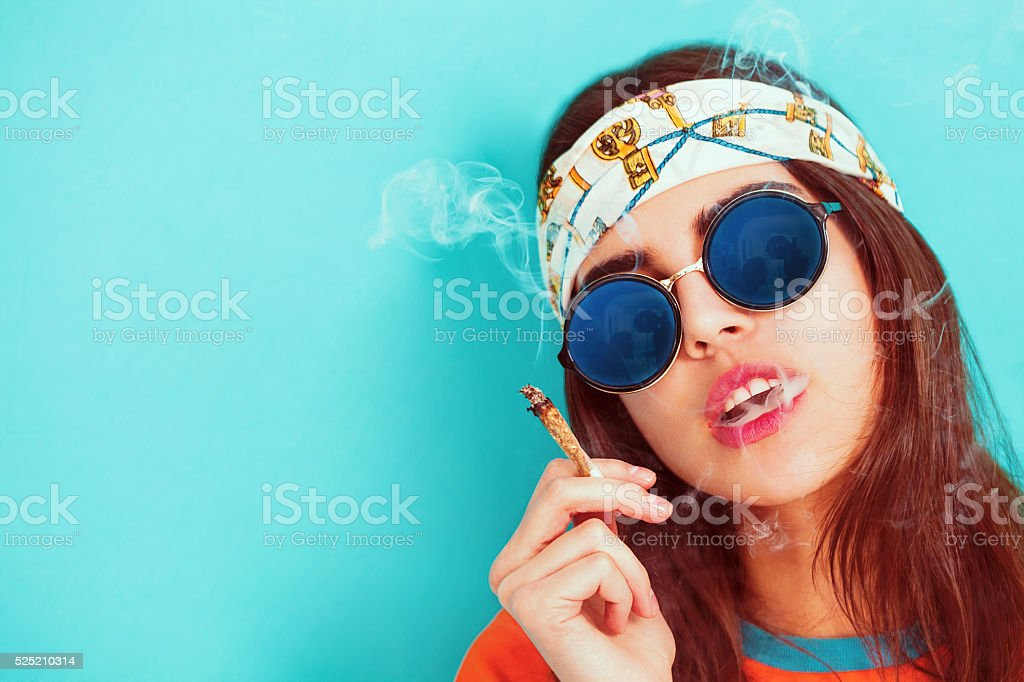 Hippie girl portrait smoking and wearing sunglasses stock photo