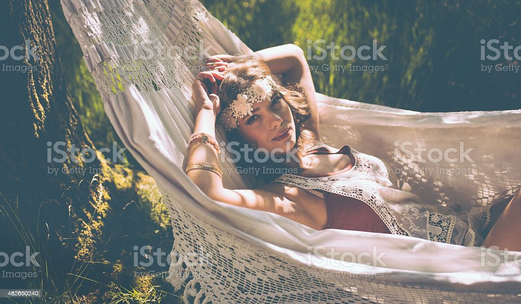 Hippie girl relaxing in a hammock in a sunlit park stock photo