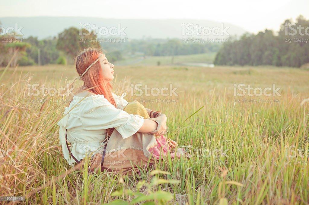 Hippie girl sitting cross-legged in golden field stock photo