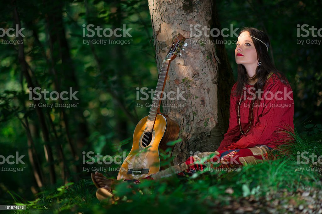 Hippie girl with the guitar in the woods stock photo