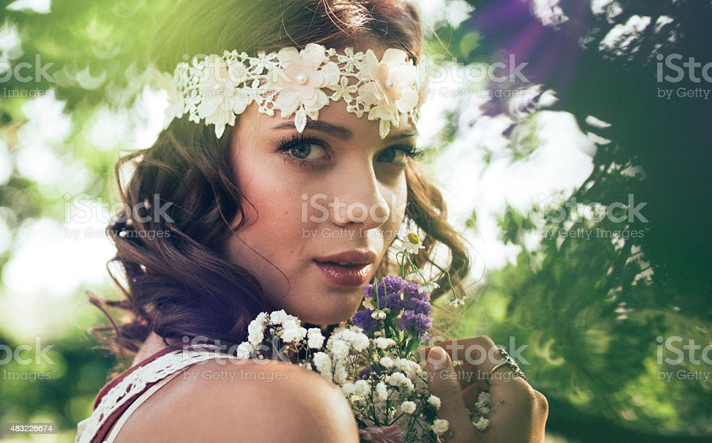 Hippie girl with wild flowers in nature stock photo