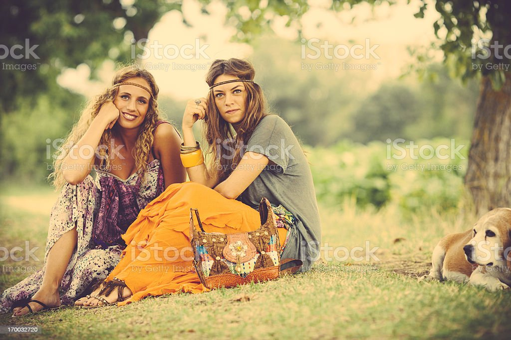 Hippie girls sitting on grass royalty-free stock photo