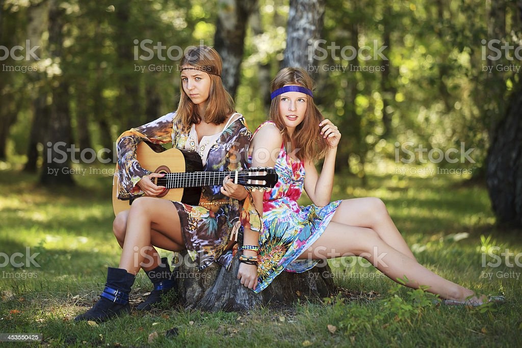 Hippie girls with guitar sitting on the stump royalty-free stock photo