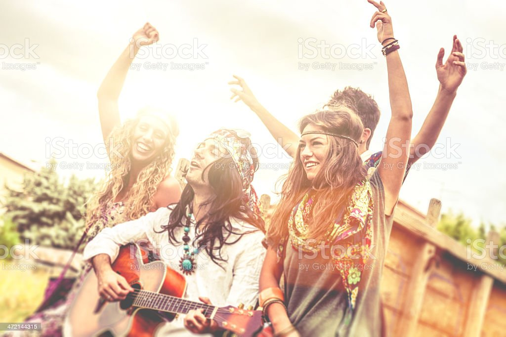 Hippie group playing guitar and dancing together stock photo