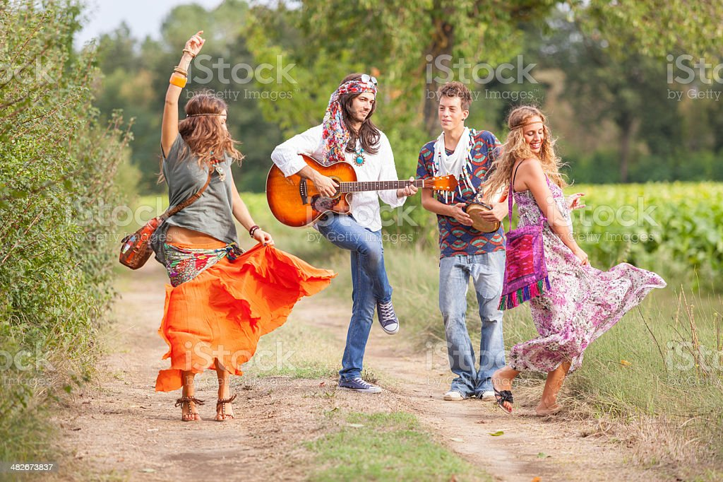 Hippie Group Playing Music and Dancing Outside stock photo