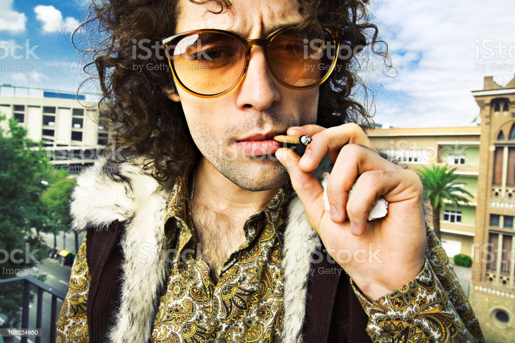 Hippie Man Smoking Marijuana Cigarette Outside royalty-free stock photo