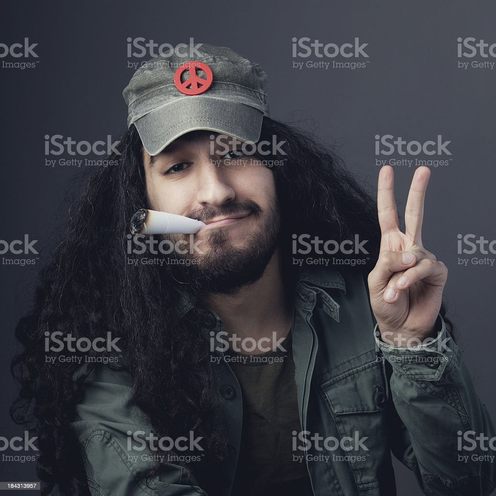 Hippie man with hat smoking large cigarette royalty-free stock photo