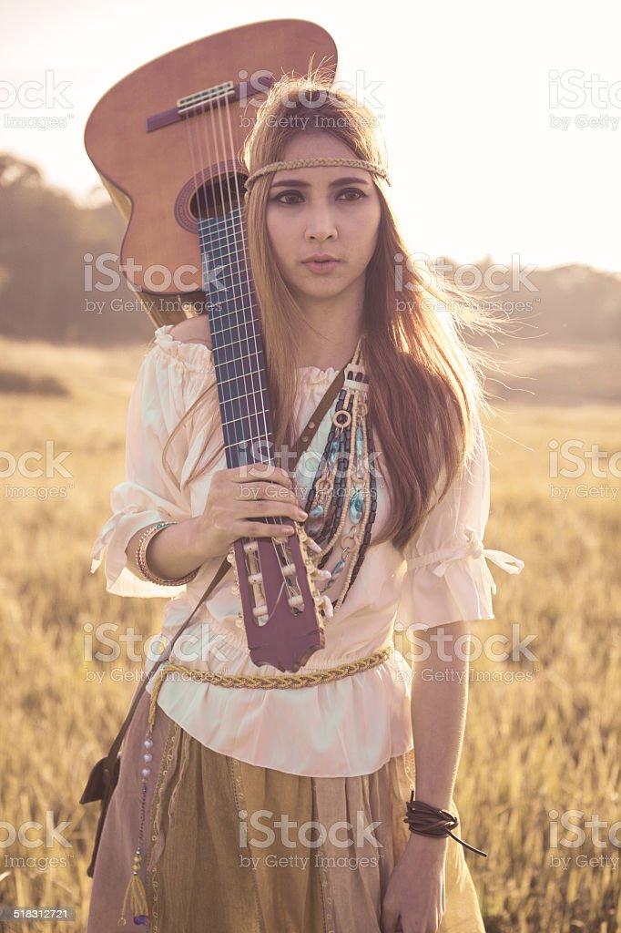 Hippie woman walking in golden field stock photo